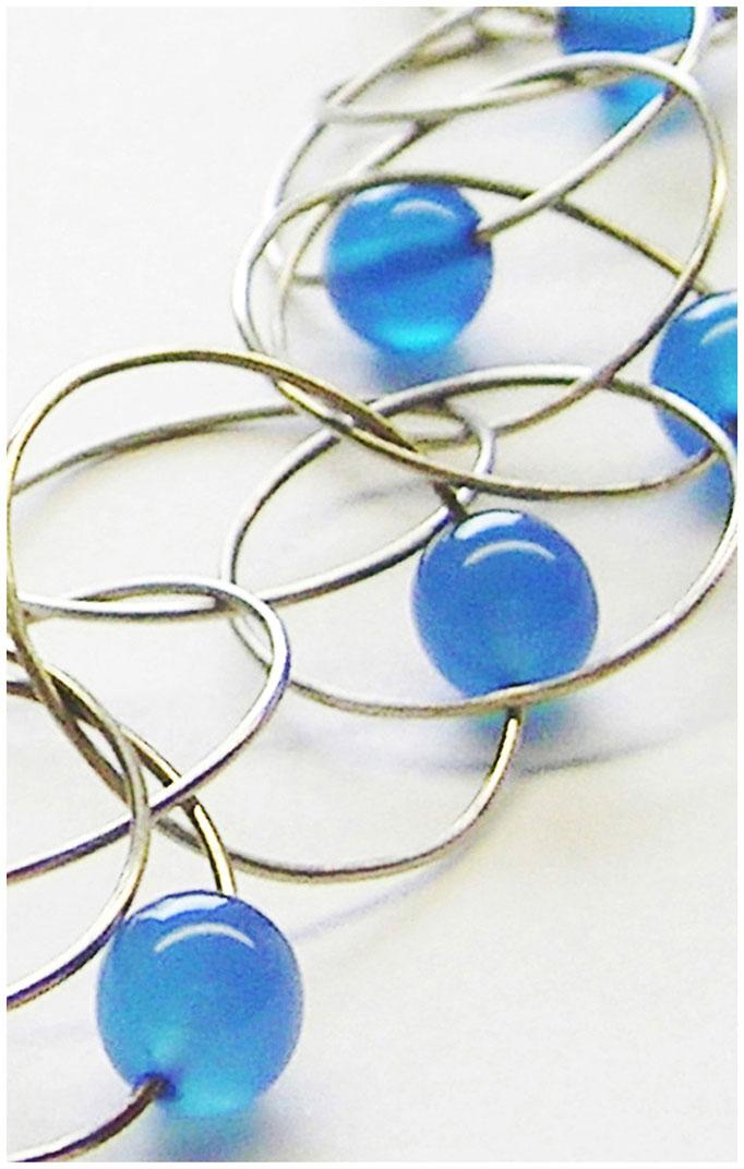Große filigrane Silberringe mit  blauen Achatperlen zu einer unkonventinellen Kette zusammengefügt