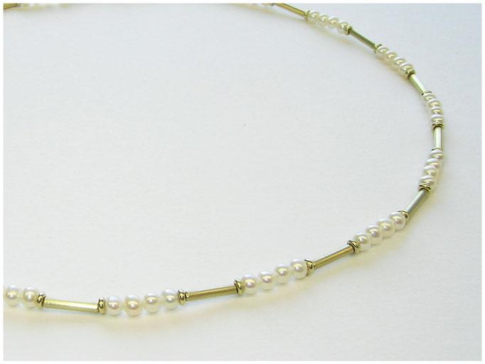 Harmonisch aufgezogene Perlenkette mit gleichmäßigen goldenen Unterbrechungen