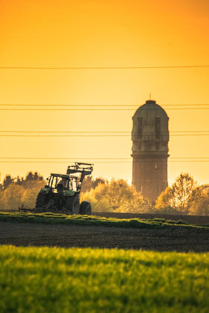 Traktor vor Bardenberger Kulisse während des Sonnenuntergangs