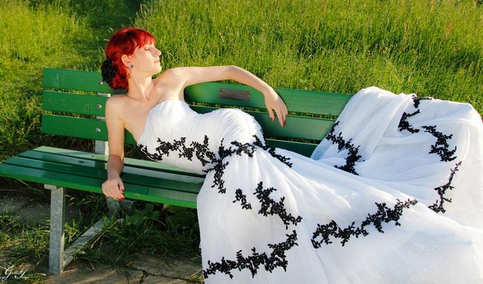 Die Braut im Meerjungfrauenkleid auf einer Bank