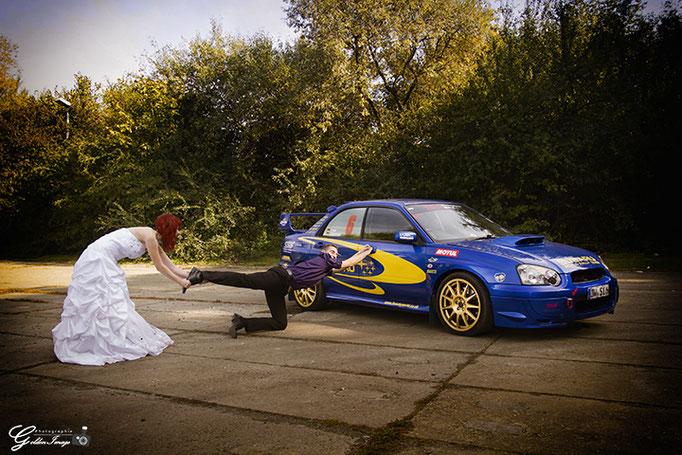 Braut zieht Bräutigam vom Auto (Subaru) weg