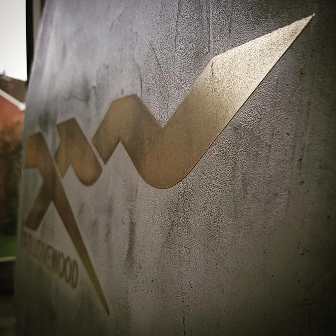 Bedrijfslogo op verouderd beton met metal stuc messing
