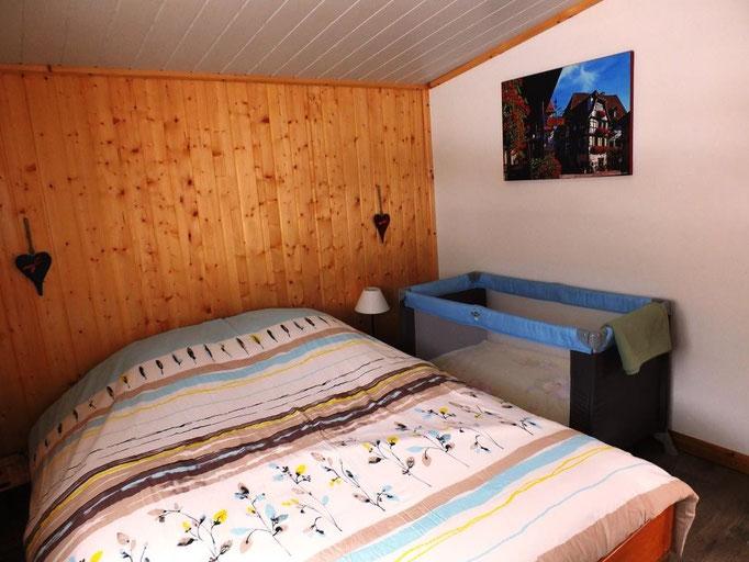 chambre avec lit bebe dans le gite de la cascade