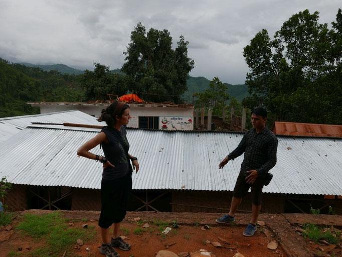 """Rajan erklärt uns, dass die temporären """"Bambusschulzimmer"""" auf dem ehemligen Schulhof errichtet wurden."""