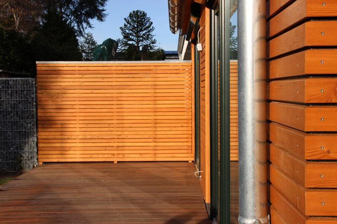Sichtschutzzaun aus Rhombusschalung passend zur Holzfassade des Anbaus in Stommeln