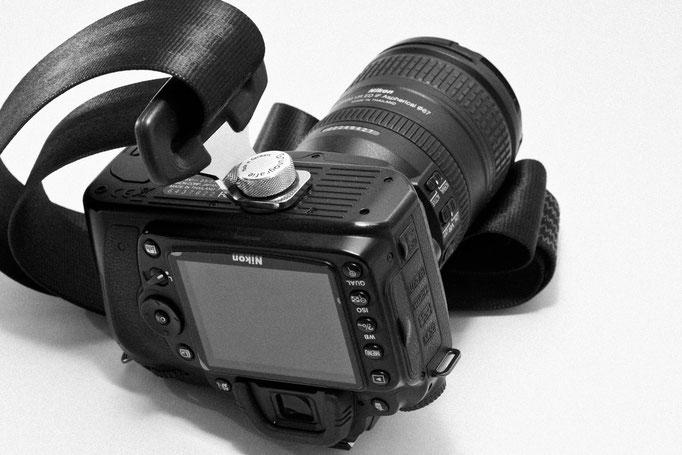 Die Kamera wird über das Stativgewinde mit dem Gurt verbunden.