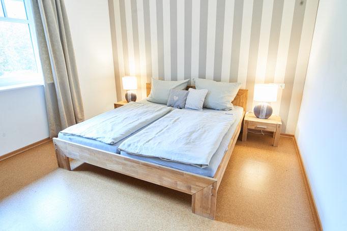 """Helles freundliches Schlafzimmer mit Doppelbett der Ferienwohnung """"Am großen Findling"""" auf dem Imkershof der Familie Röhrs in Schneverdingen-Surbostel"""
