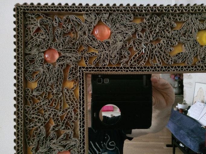 Miroir avec encadrement en frisottis de carton sur fond de papier jaune-orangé.