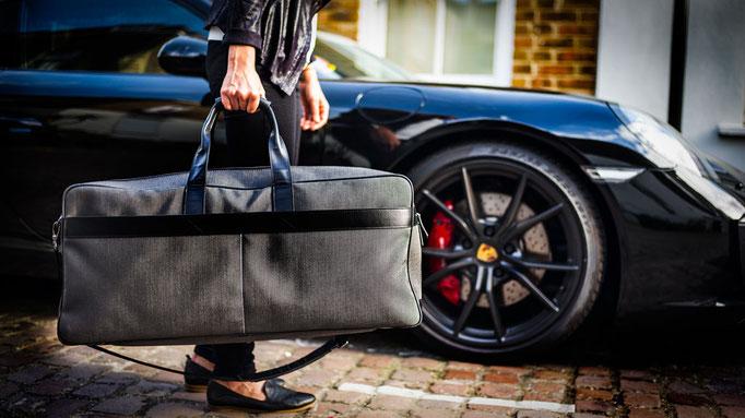 Der Epirus London Weekender vor Porsche