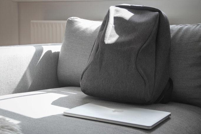 Diebstahlsicherer Rucksack mit Macbook auf designer Sofa