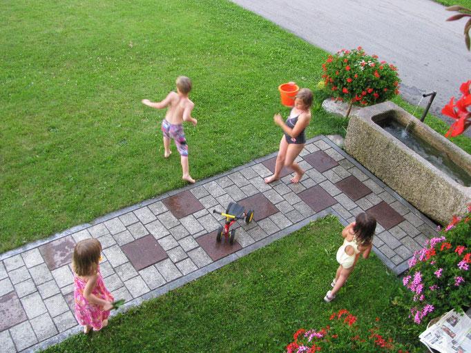 Die Gästekinder spielen mit Wasser im Garten