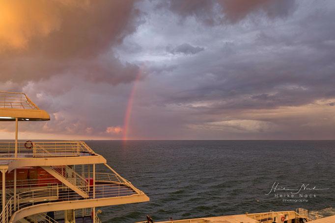 Sonnenaufgang mit Regenbogen auf der Nordsee