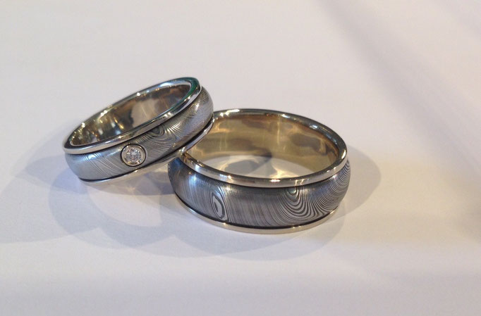 Trauringe aus Damasten mit Inlay und Rand aus Weißgold 585/-, im Damenring Brillant 0,03 ct