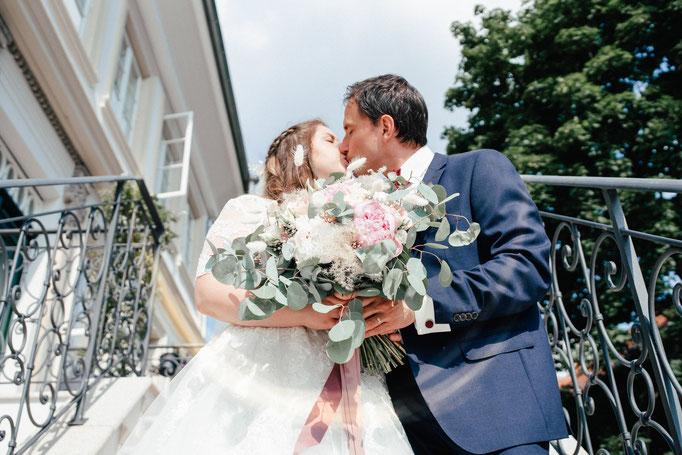 küssendes Brautpaar vor dem Hotel Wyndberg