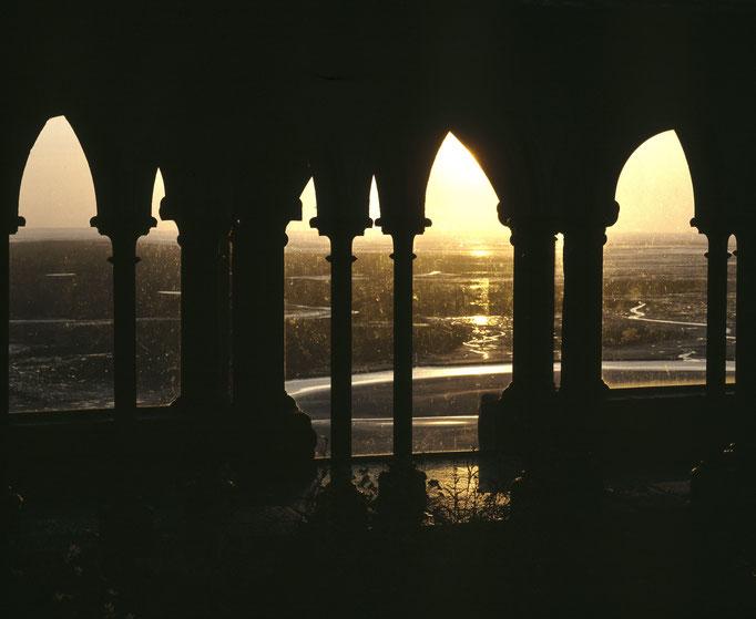 La baie du Mont-Saint-Michel au crépuscule vue à travers les baies de la façade occidentale du cloître