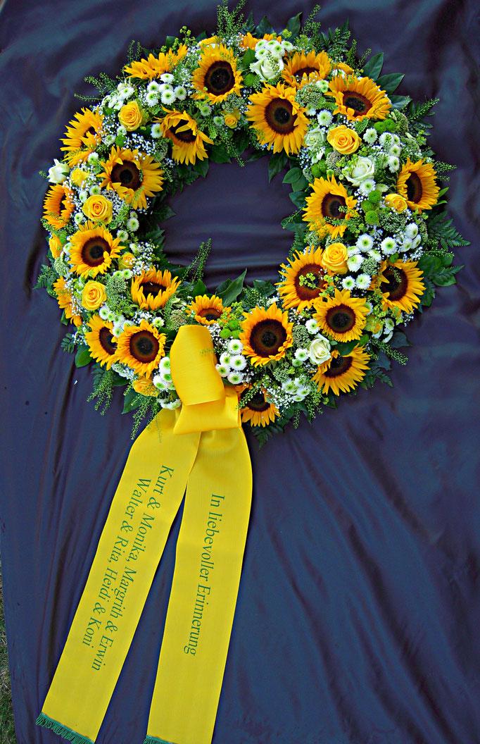 Blumenkranz mit Trauerscherpe