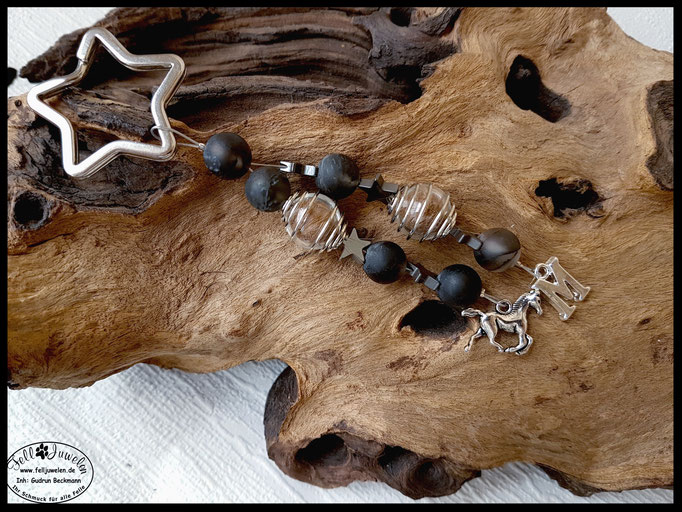Bild 46: Eingefasste Pferdehaare in eine Glasperle und von einem silbernen Perlenkäfig umrandet. Verarbeitet sind marmorierte Perlen und Hämatitsternchen. Als Hingucker dienen zum Abschluss ein Pferdeanhänger und ein Buchstabenanhänger . Preis: 40 Euro