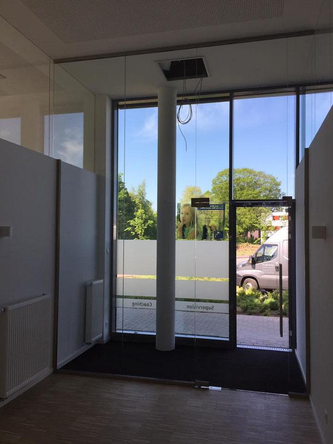 Deckenhoher Raumteiler als Windfang im Eingangsbereich