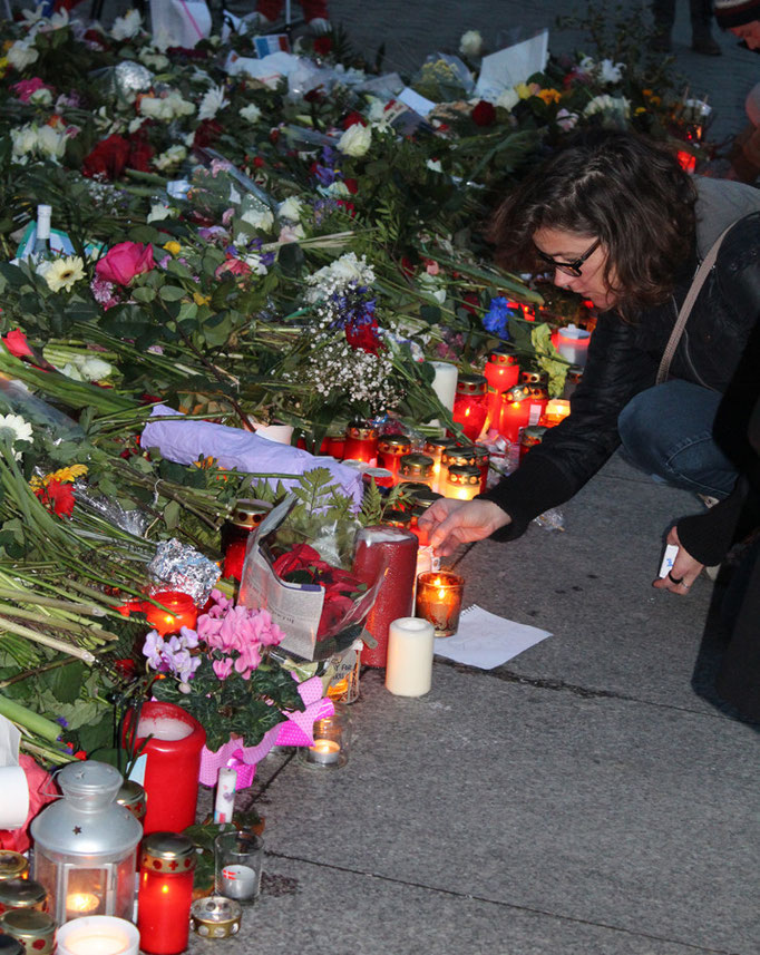 Eine Frau zündet ein Licht an vor den Blumen vor der französischen Botschaft in Berlin. Foto: Helga Karl