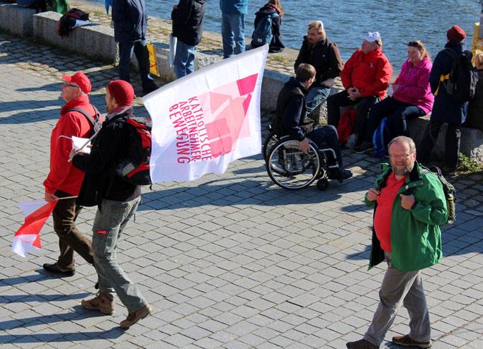 """Menschen mit Fahne """"Katholische Arbeitnehmerbewegung"""" am Spree-Ufer gehen zum Sammlungsplatz. Großdemo Stop TTIP Berlin am 10.10.2015.  Foto: Helga Karl"""