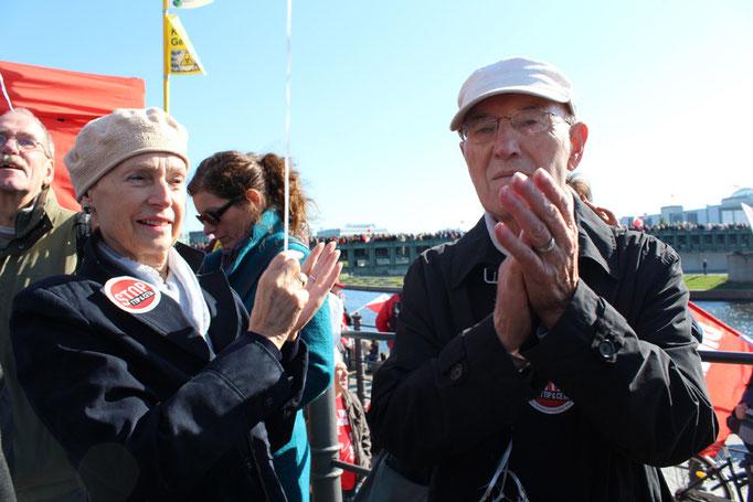 Ein älteres Ehepaar klascht bei den Reden der Auftaktkundgebung vor dem Demo-Start. Großdemo Stop TTIP Berlin am 10.10.2015.  Foto: Helga Karl