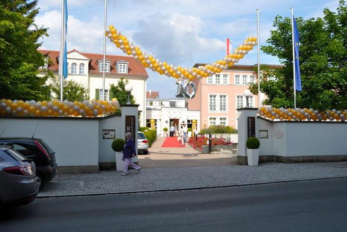 Hängender Ballonbogen mit Zahl und Ballongirlande auf der Mauer. Viele unterschiedliche Ausführungen und Farben der Ballongirlande möglich. Villa Geyerswörth.