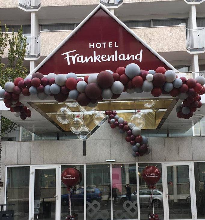 Verschiedene organic Girlanden am Vordach und über dem Eingang. Riesenballons mit Logo auf Säulen. Bubble Ballons mit Lichterketten im Giebel. Hotel Frankenland.