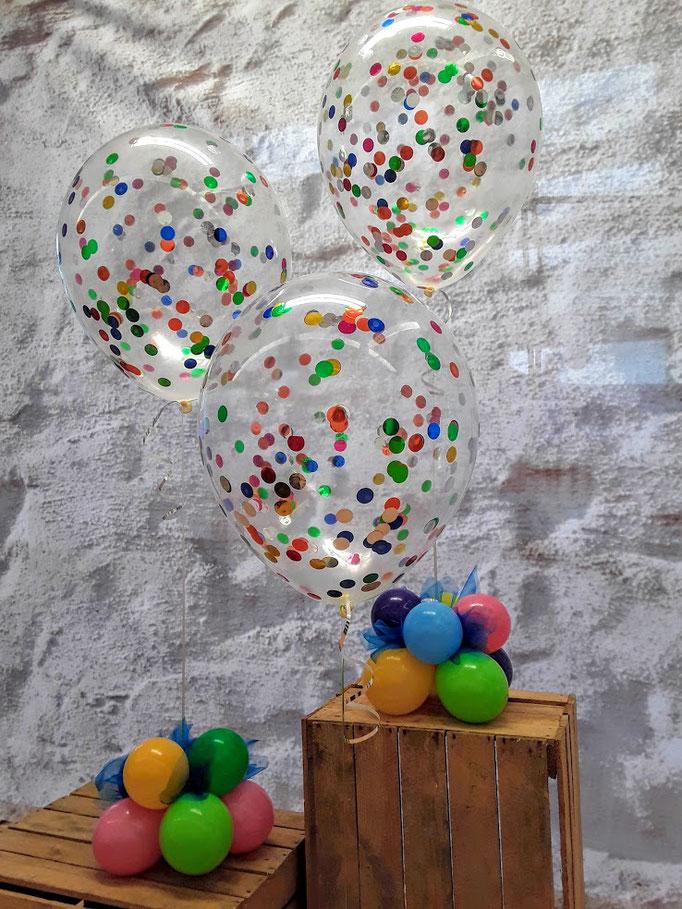 Variation aus kunterbuntem Konfettiballons. DAs Gewicht ist ein kleiner bunter Ballonfuß. Eine farbenfrohe Tischdekoration für fröhliche Anlässe.