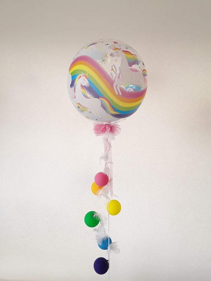 Einhorn-Bubble Ballon mit bunten hängenden Regenbogen Ballons.