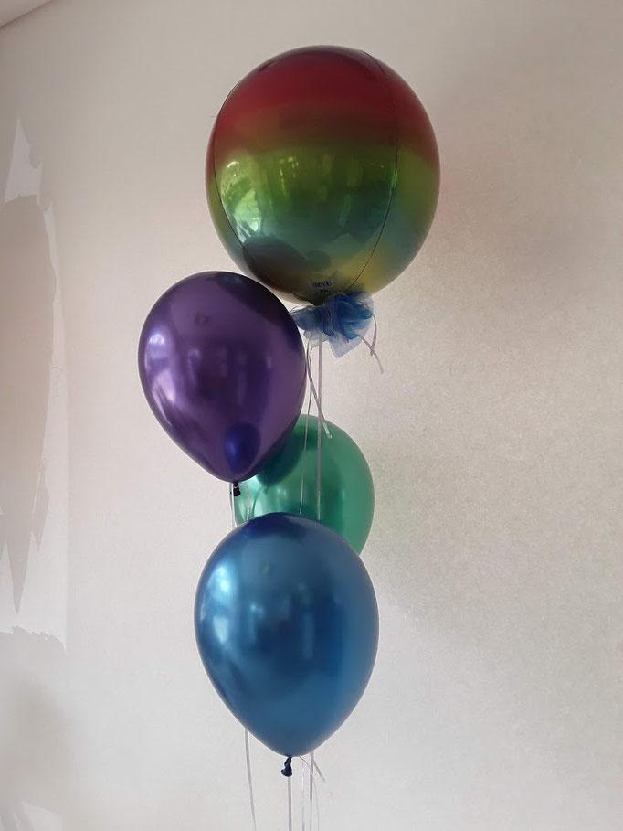 Der regenbogenfarbene, komplett runde Ballon ist neu im Sortiment. Darunter farblich passende Chrome-Latexballons.