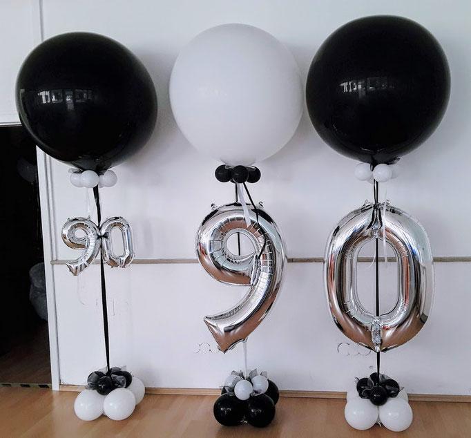 Schwarze und weiße Riesenballons luftgefüllt auf einer Säule. Im GEsamtbild eine sehr exklusive Dekoration zum 90. Geburtstag.