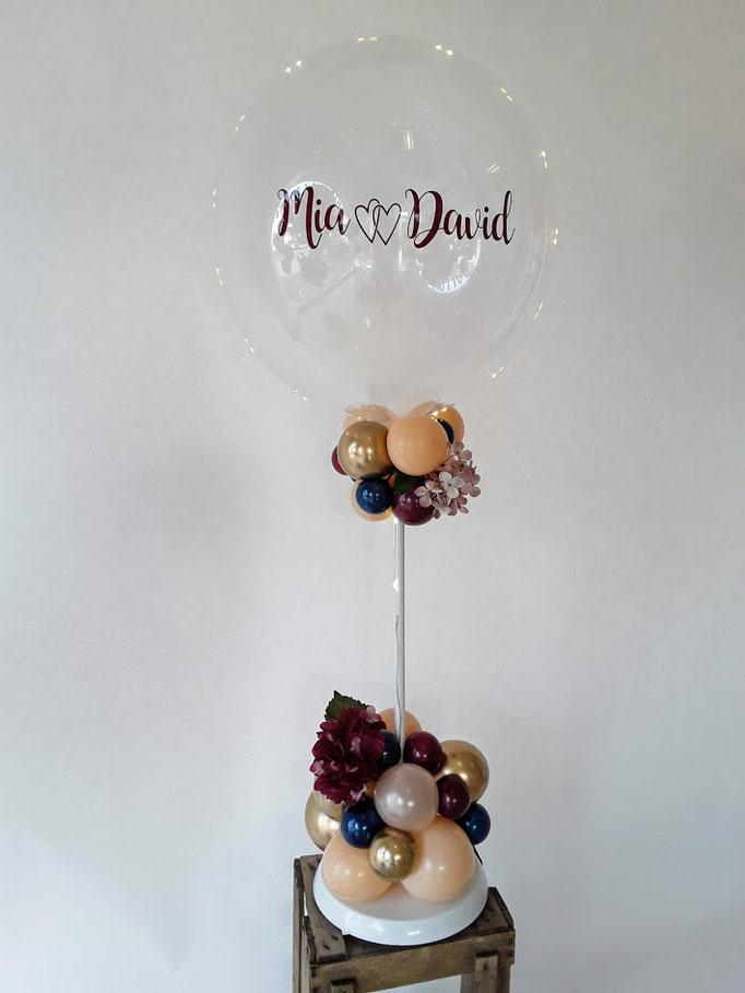 Durchsichtiger Bubble-Ballon am Ständer, verziert mit kleinen Latexballons. Das Highlight: Der Bubble ist mit dem Namen vom Brautpaar beschriftet.