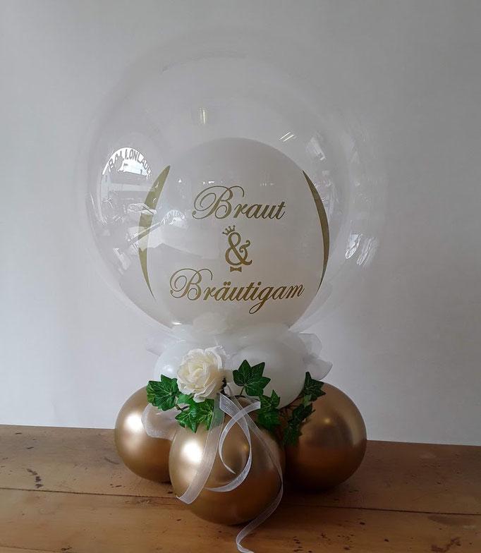 Elegantes Tischbouquet mit einem Ballon-in-Ballon-Topping und einer Rose. Die durchsichtige Außenhülle macht es besonders wertig und chic.