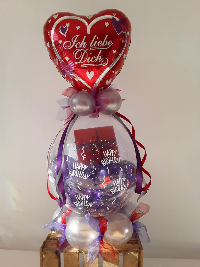 Das Geldgeschenk ist im Verpackungsballon eingebracht. Ein Verpackungsballon hat ein Topping aus Folienballlons oder Latexballons, wird mit weiteren Ballons oder Konfetti gefüllt. Hier mit Ballon-Standfuß.