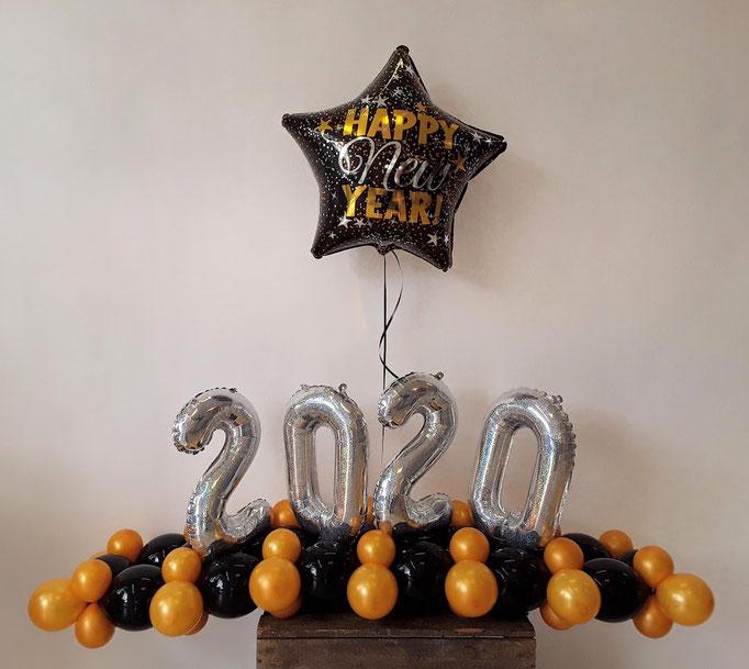 Feiern Sie das neue Jahr gebührend. Tischbouquet mit passender Jahreszahl. Als Highlight schwebt noch ein Stern über den Zahlen.