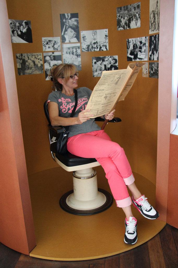Nicole auf dem Friseurstuhl mit Zeitung.