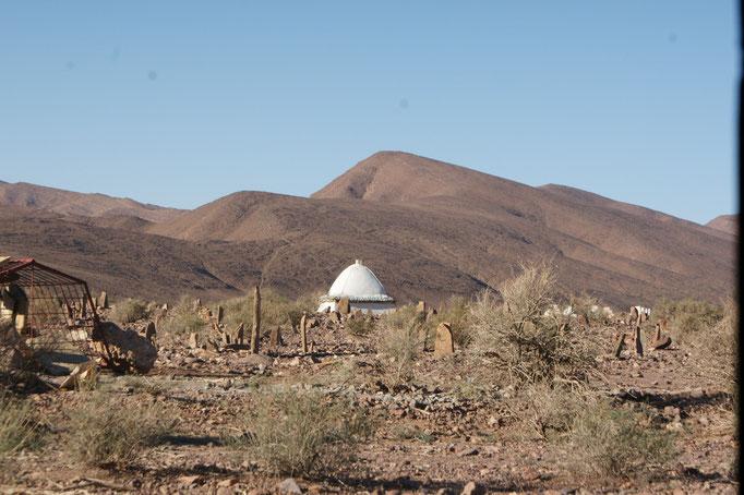 Hinten Marabu, vorne Friedhof. Links ein frisches Grab, das vor den Tieren geschützt wird.