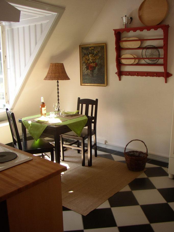 Die Küche der Ferienwohnung mit schwarz weißem Fliesenboden ist urgemütlich