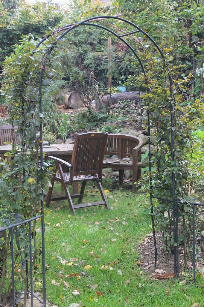 Der Torbogen als Eintritt zum kreisförmigen Gartenbereich