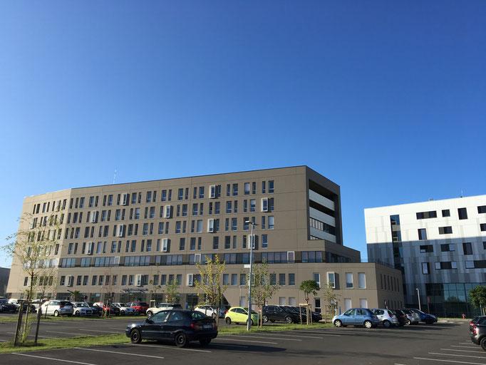 Bâtiment de consultation en gris foncé, relié par une chicane au RDC au bâtiment de la clinique en gris clair