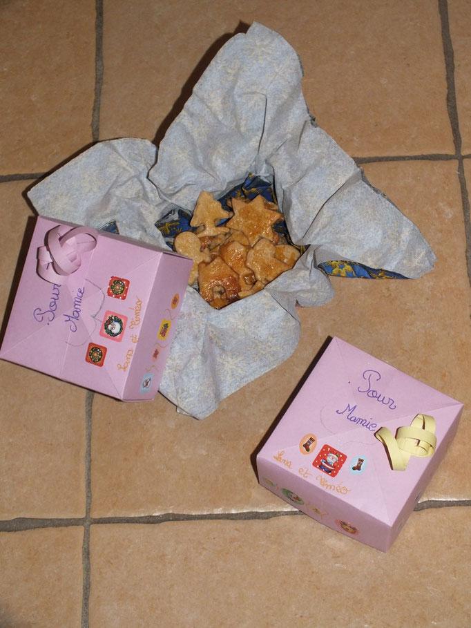 Boîte papier pour petits sablés à la cannelle pour Noel : 2 boîte en origami, faites avec un carré de papier épais et un autre de 8 mm de moins pour celle du dessous, décorée par les enfants, remplie de sablés faits par les enfants.
