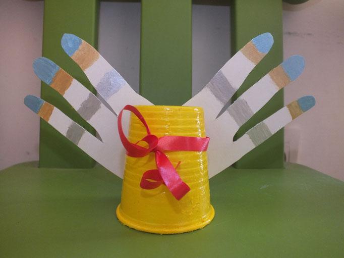 Une clôche de Pâques : un verre en plastique peint avec de l'acrylique, et ailes en carton (une partie d'une empreinte de main)