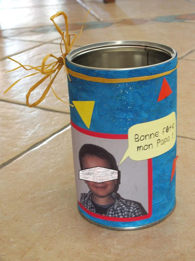 Pot à crayon, avec pot à café, recouvert d'une feuille cartonnée peinte et décorée de gommettes et une photo de l'enfant