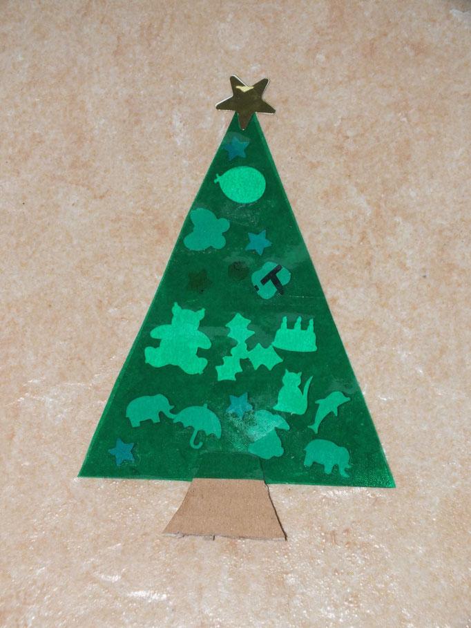 Sapin de Noel pour vitre, réalisé avec 2 triangles de plastique transparent adhésif de couleur verte, l'enfant n'a qu'a déposer  des formes en papier venant d'emporte pièces. Avant de refermer, placer un morceau de carton marron pour le tronc