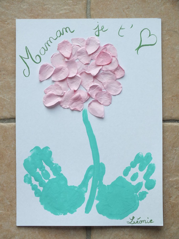 une fleur en colage de pétale de papier , empreintes de mains en peinture pour faire les feuilles, pour la fête des mères