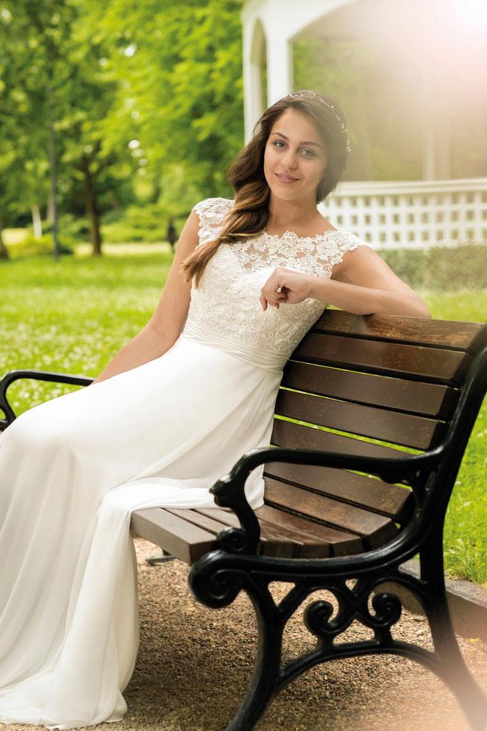 Braut sitzt auf Bank