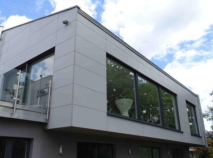Haus Ammerdung: Graue Flächen, unterteilt durch Schattenfugen und große Fensterflächen verbinden sich zu moderner Architektur