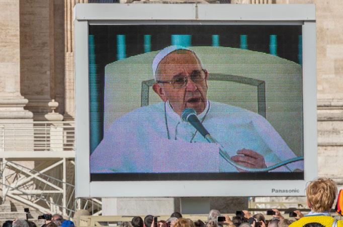 Während der Generalaudienz ist Papst Franziskus auch auf Videowänden zu sehen