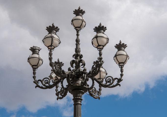 Ein filigraner Kandelaber streckt sich über den Petersplatz in den weißblauen Himmel