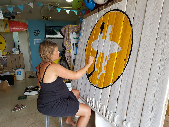 Annika designing and painting our new driftwood banner...